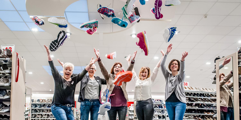 Verkäuferinnen werfen Schuhe bei SCHUH OKAY